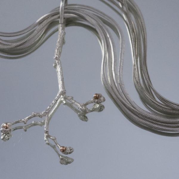 vienetinis pakabukas šakelė iš sidabro, puošta aukso burbuliukais.