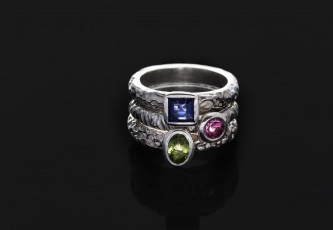 Sidabriniai žiedai su skirtingais akmenukais.