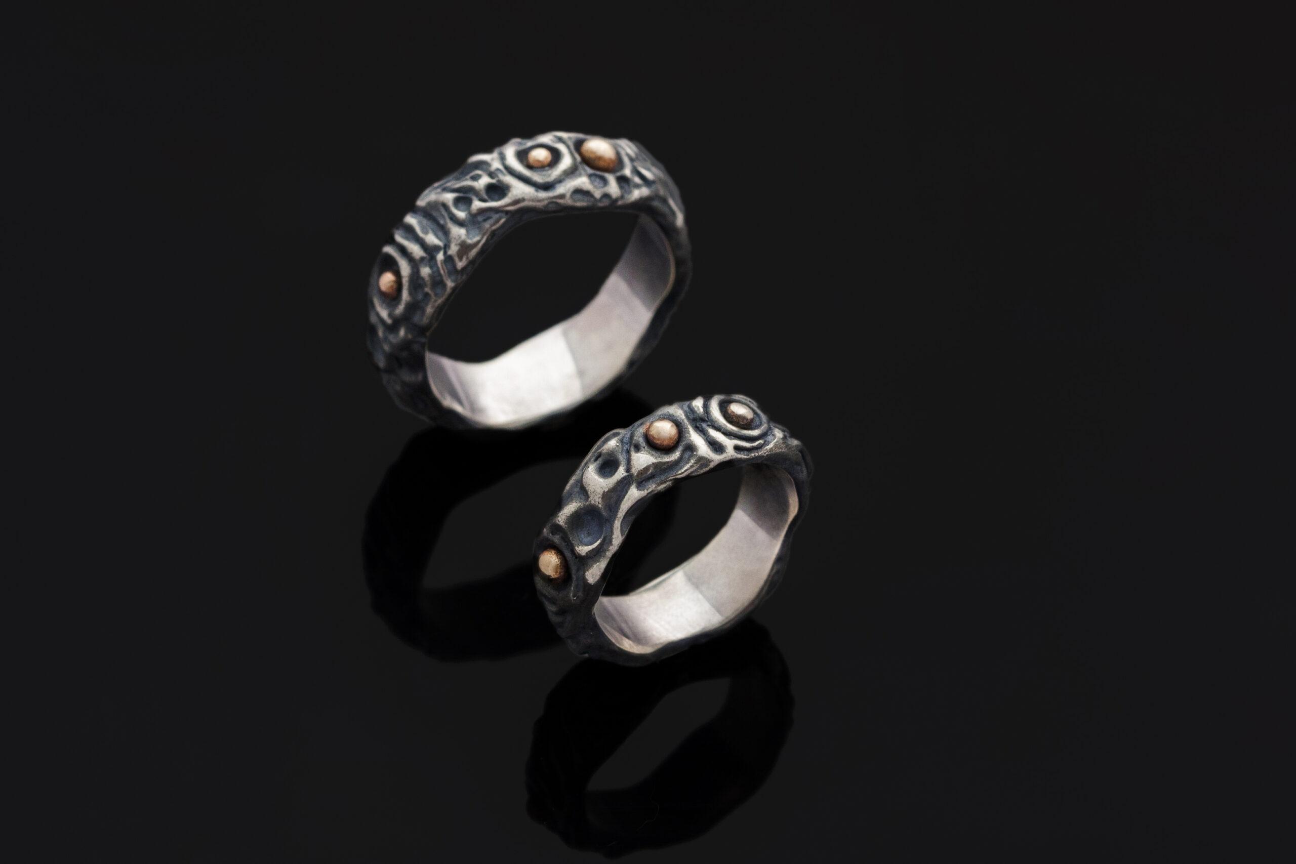 Sidabriniai vestuviniai žiedai su aukso detalėmis.