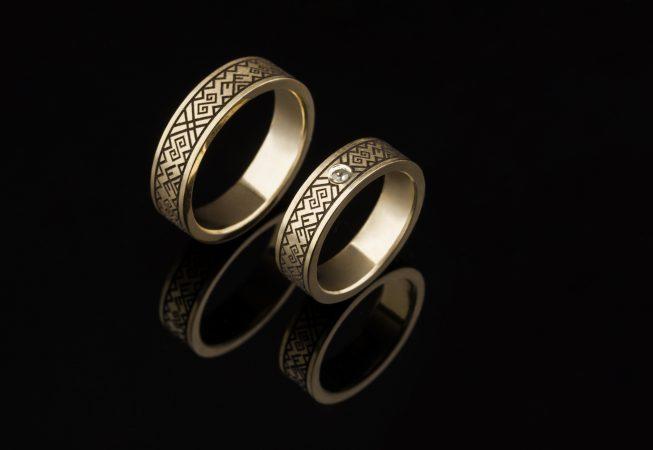 Vienetiniai vestuviniai žiedai su baltų simboliais.